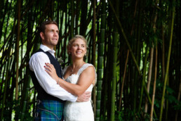 Wedding portrait photo of Bobby and James standing in bamboo forest at Chateau La Gauterie in France