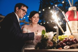 Bride and groom cutting tiered wedding cheese presentation that is lit with sparklers at night