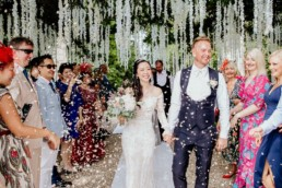 Chinese bride and groom holding hands, walking up aisle under tree with white flower gardens and confetti being thrown